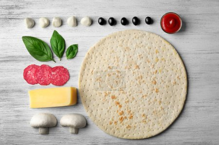Photo for Raw pizza ingredients on wooden background, top view - Royalty Free Image