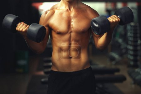 Athletic man training with dumbbells