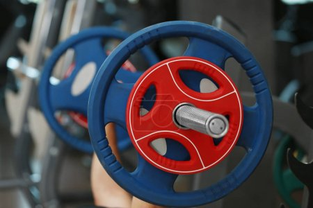 Athletic man training with barbell in gym...