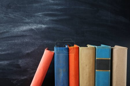 Photo for Stacked Books and blackboard on background - Royalty Free Image