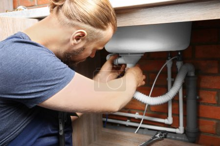 Portrait of handsome plumber repairing sink pipes