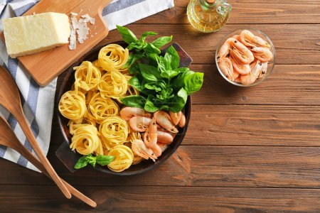 Pan with ingredients for tasty pasta, napkin and kitchen board on wooden table, top view