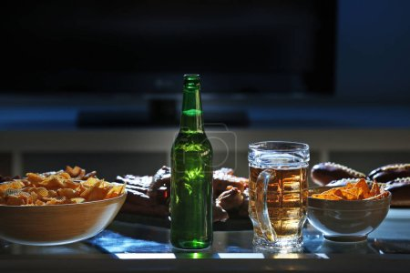 Tasty snacks and beer on kitchen table against blurred background