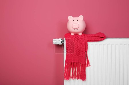 Piggy bank and scarf on heating radiator on pink background