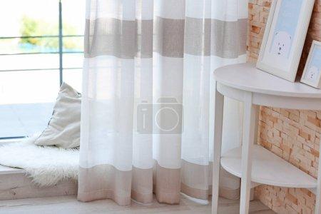 Photo pour Rideaux à rayures colorées, table et seuil de fenêtre bas avec oreiller et tapis - image libre de droit