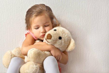 Photo pour Triste petite fille avec ours en peluche sur fond clair - image libre de droit