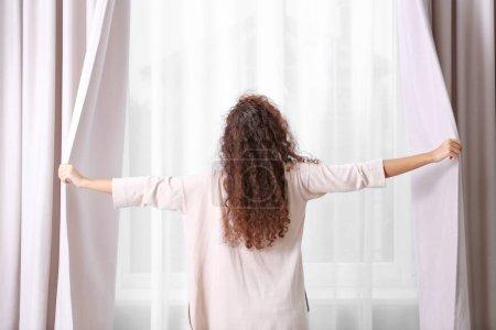 Photo pour Femme ouvrant rideaux dans la chambre - image libre de droit