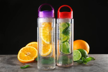 Water with citrus fruits in bottles