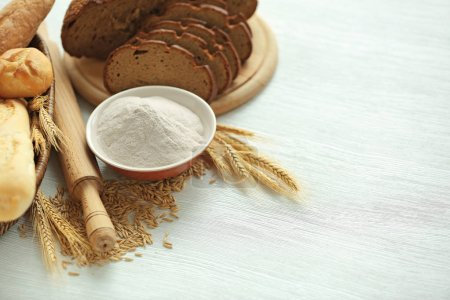 Bread slices with wheat flour, spikes and grains on white table