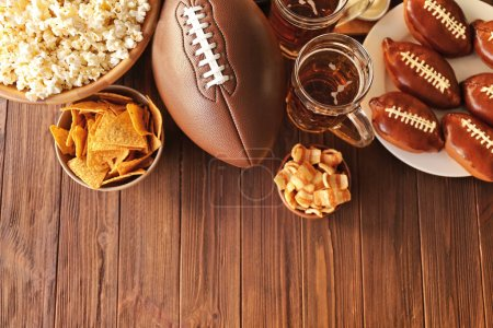 Photo for Table full of tasty snacks and beer prepared for watching rugby on TV - Royalty Free Image