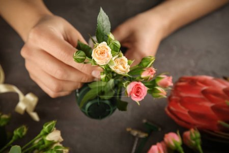 Photo for Female hands making beautiful bouquet of flowers on dark background - Royalty Free Image