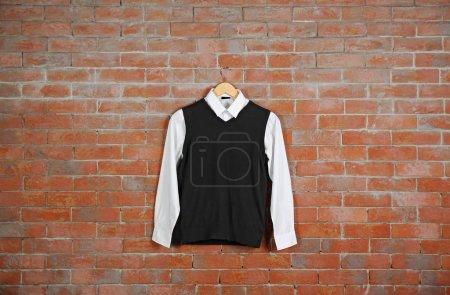 School uniform on brick wall