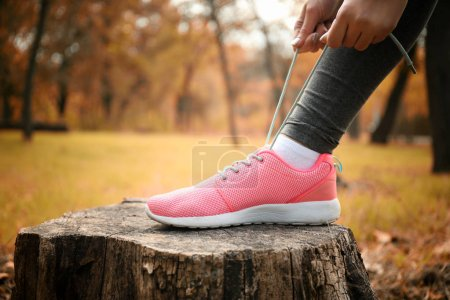 Woman tying up jogging shoes