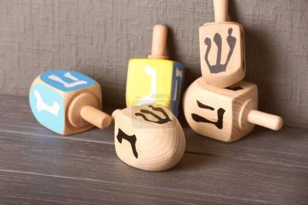 Photo pour Dreidels en bois pour Hanoukka sur table en bois contre mur texturé gris - image libre de droit