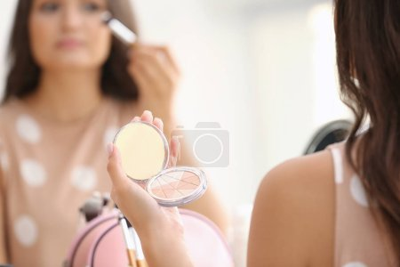 Girl applying cosmetics