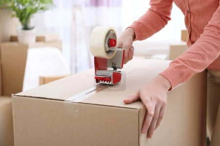Photo for House moving concept. Closeup of woman packing cardboard box - Royalty Free Image