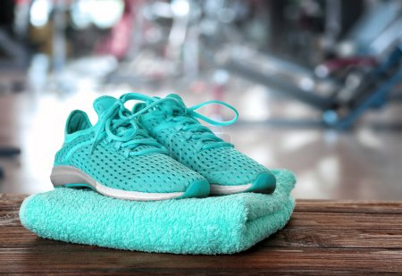 Sport shoes and towel on table