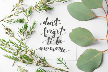 """Photo for Quote """"Dont forget to be awesome"""" written on paper with leaves and flowers on white background. Top view - Royalty Free Image"""