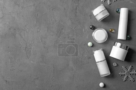 Photo pour Produits cosmétiques de beauté avec décoration de Noël sur fond gris - image libre de droit