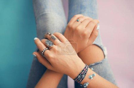 Photo pour Mains féminines avec des bijoux sur fond de couleur - image libre de droit