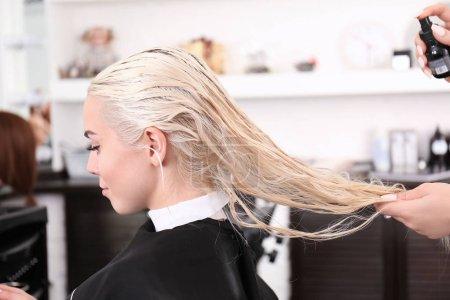 Photo pour Coiffeur utilisant le baume sur les cheveux blonds au salon - image libre de droit