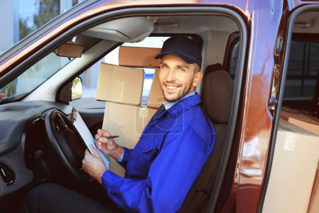 Photo for Delivery man checking list in car with parcels - Royalty Free Image