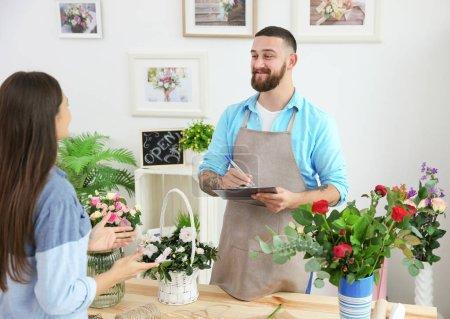 Handsome florist accepting order