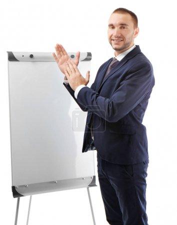 Photo pour Jeune entrepreneur applaudir près de chevalet sur fond blanc - image libre de droit