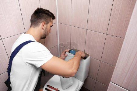 Photo for Plumber repairing toilet cistern at water closet - Royalty Free Image