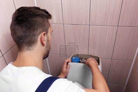 Plumber repairing toilet