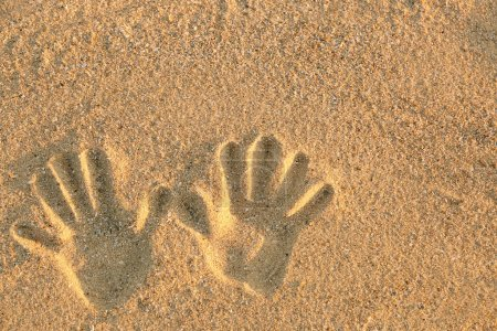 Hand prints on sea sand