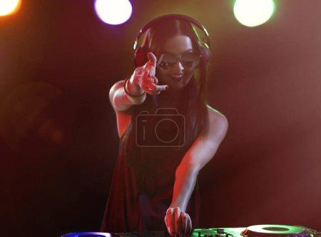 Photo pour Jolie jeune Dj jouant de la musique en boîte de nuit - image libre de droit