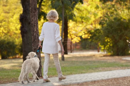 Senior woman walking with dog