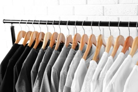 Photo for Black, grey and white t-shirts on hangers against brick wall, close up view - Royalty Free Image