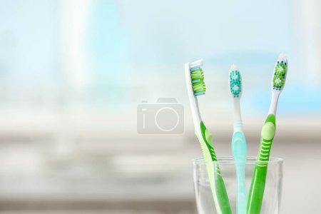 Photo pour Brosses à dents colorées en verre sur fond flou - image libre de droit