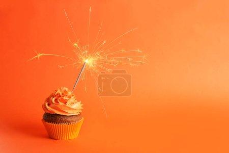 Foto de Dulce sabroso cupcake con luces de Bengala sobre fondo naranja - Imagen libre de derechos