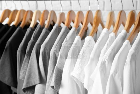 Photo for Black, grey and white t-shirts on hangers, close up view - Royalty Free Image