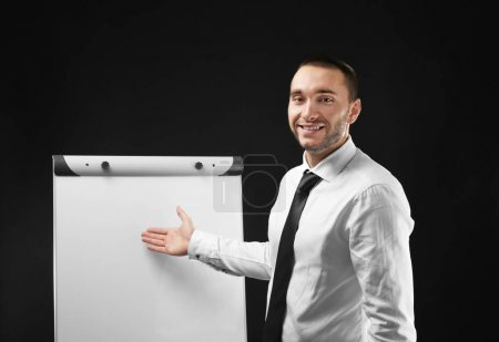businessman standing near flip chart