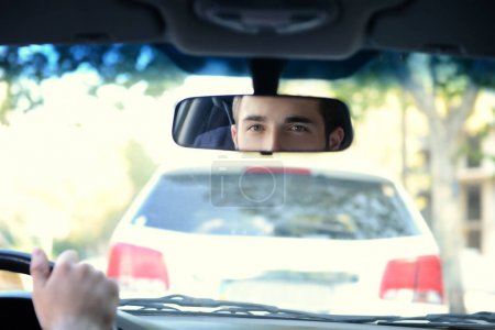 Photo for Young successful driver looking in rear view mirror - Royalty Free Image