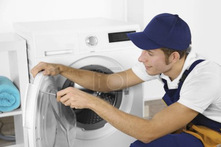 Photo for Young handsome Plumber repairing washing machine - Royalty Free Image