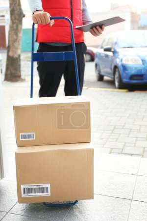 Courier holding cart with parcels