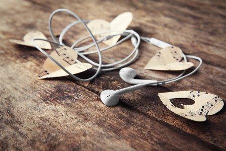 Photo pour Coeurs en papier avec notes de musique et écouteurs sur fond en bois - image libre de droit