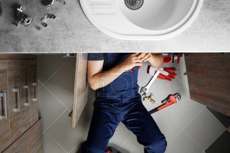 Male plumber repairing sink pipes