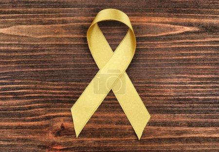 Photo pour Ruban d'or sur fond en bois. Notion de cancer enfants - image libre de droit