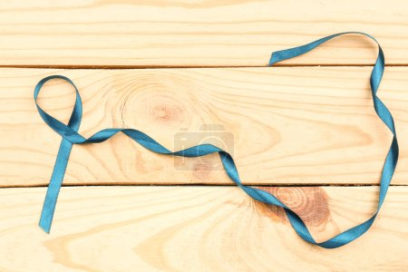 Sea-green ribbon on wooden background.