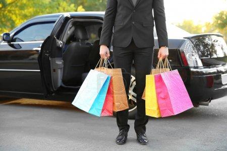 Photo pour Chauffeur tenant des sacs colorés et debout près de voiture de luxe - image libre de droit