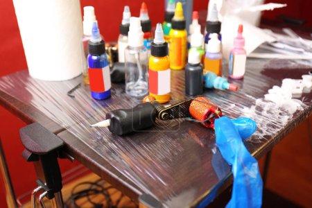 Tätowiermaschine und Flaschen mit bunten Tinten