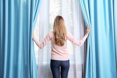 Photo pour Jeune fille ouverture rideaux - image libre de droit