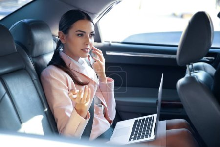 Photo pour Femme d'affaires parlant par téléphone portable et en voiture - image libre de droit