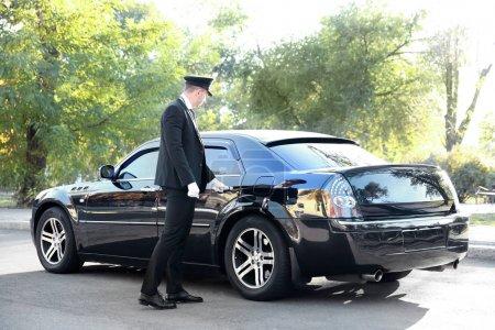 Photo pour Chauffeur ouvrant la porte de la voiture dans la rue - image libre de droit